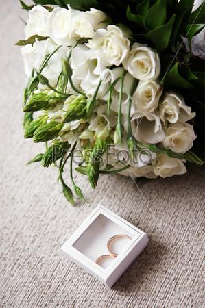 Маленькая декоративная коробочка с обручальными кольцами рядом с букетом белых роз
