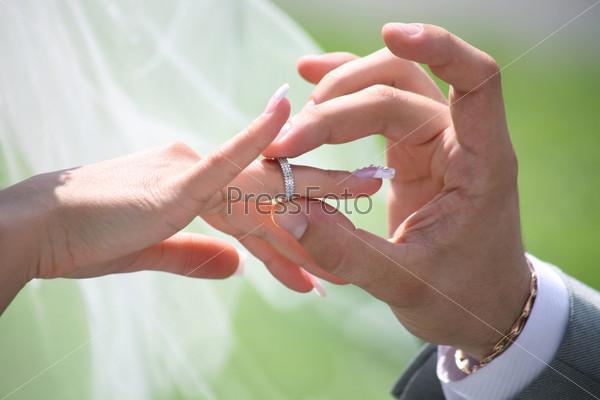 Жених одевает обручальное кольцо на палец невесты