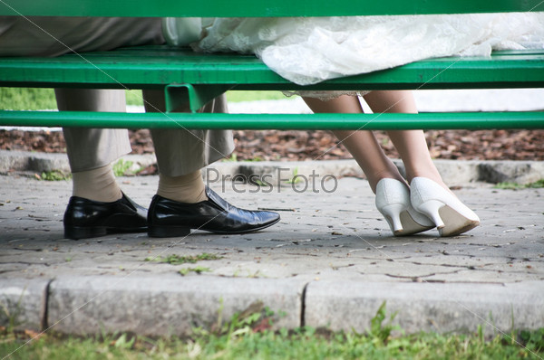 Ноги новобрачных на скамейке в парке