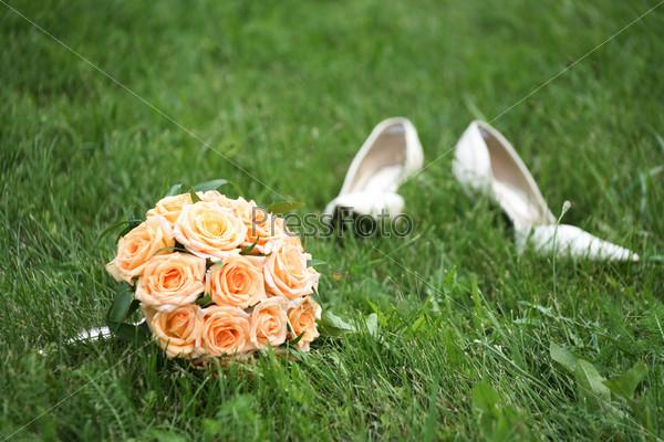 Букет невесты и ее белые свадебные туфли на зеленой траве