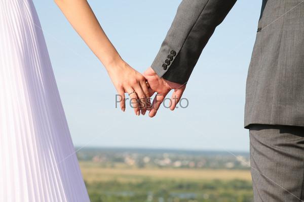 Новобрачные держатся за руки