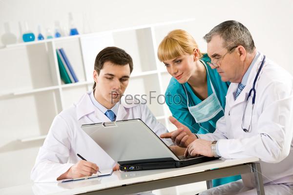 Пожилой доктор указывает коллегам на экран ноутбука
