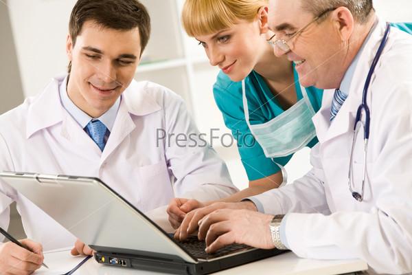 Три терапевта смотрят на экран ноутбука