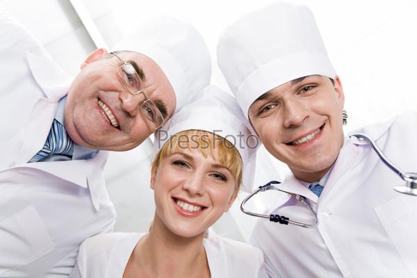 Три практиканта, улыбаясь, смотрят в камеру