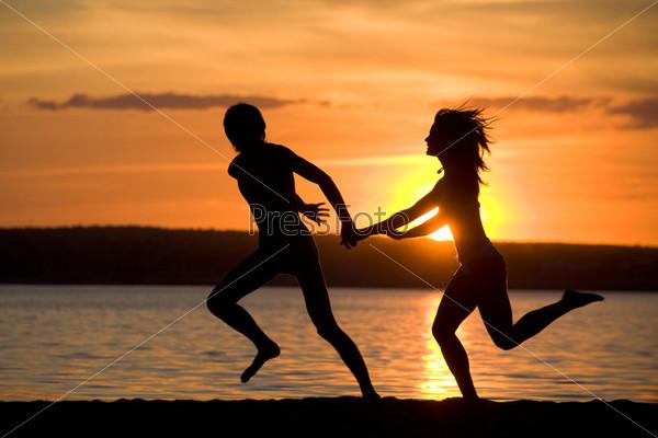 Силуэты счастливой пары, бегущей по побережью, на фоне заката