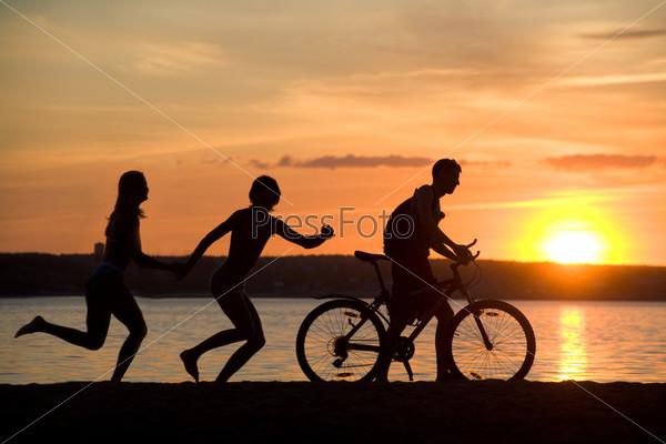 Фотография на тему Силуэты счастливой пары и велосипедиста на побережье на фоне заката