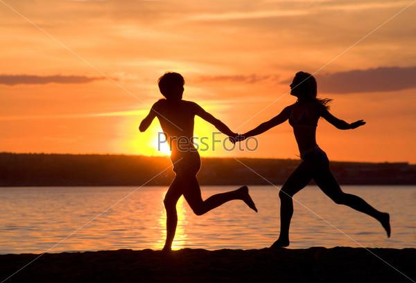 Счастливые парень и девушка бегут по берегу на фоне восхитительного заката