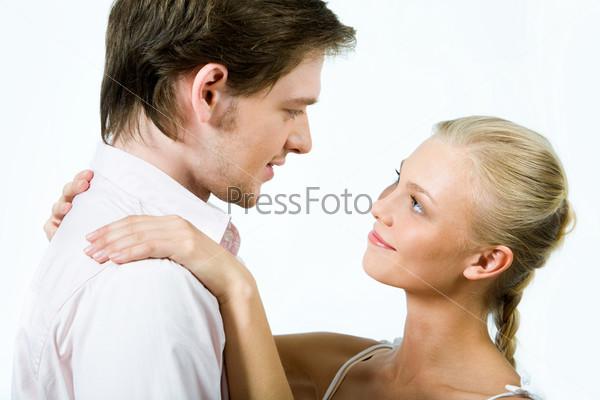 Привлекательный молодой человек смотрит на симпатичную блондинку, обнимающую его за плечи