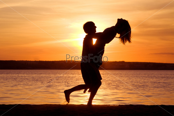 Фотография на тему Молодой человек поднимает на руках девушку на фоне восхитительного заката