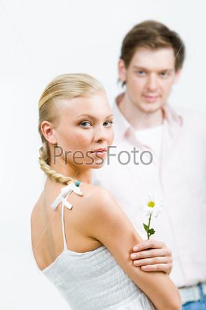 Симпатичная блондинка держит в руке белый цветок на фоне молодого человека