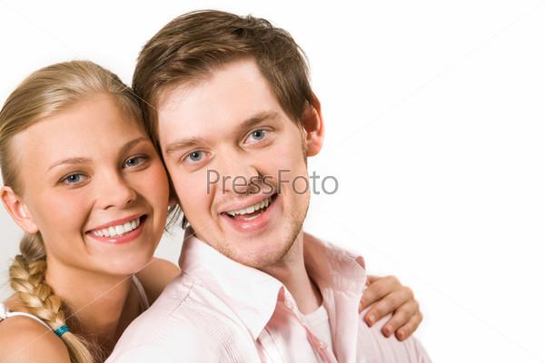 Счастливая пара улыбается и смотрит в камеру