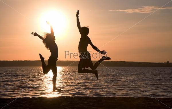 Влюбленная пара подпрыгивает на бегегу озера на фоне восхитительного заката