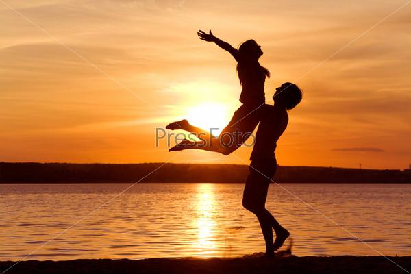 Молодой человек поднимает на руках девушку на фоне заката