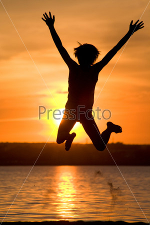 Радостный молодой человек прыгает и поднимает руки на фоне заката на берегу озера