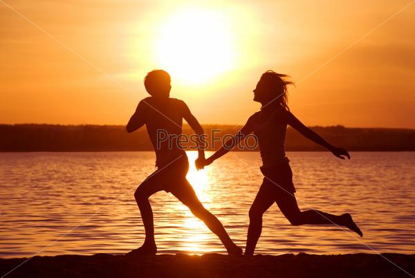 Счастливые влюбленные бегут по берегу озера на фоне заката
