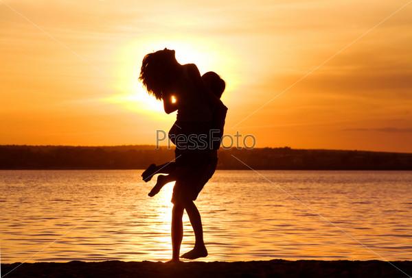 Счастливый молодой человек держит на руках, стоя на берегу озера