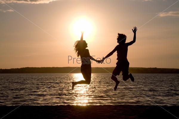 Счастливая пара резвится на берегу озера на фоне восхитительного заката