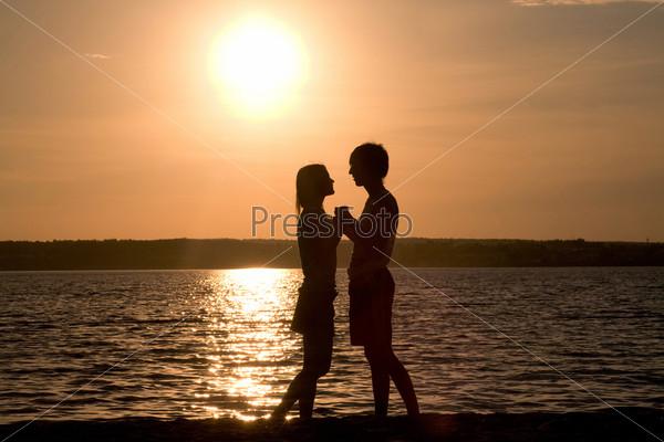 Романтичная пара смотрит друг на друга на берегу озера