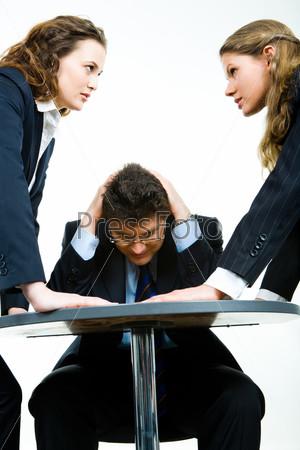 Бизнесмен сидит за столом, схватившись за голову, между двумя девушками в деловых костюмах