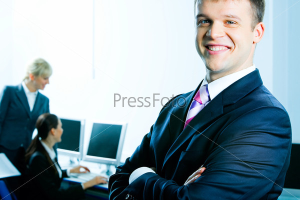 Счастливый молодой человек стоит на фоне девушек, работающих за компьютером, и улыбается