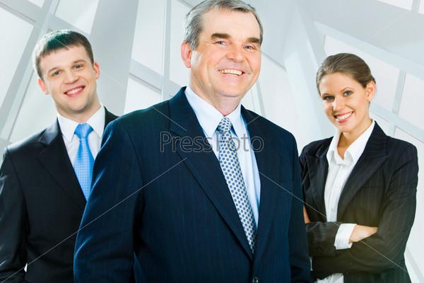 Пожилой начальник стоит на фоне своих молодых сотрудников и улыбается