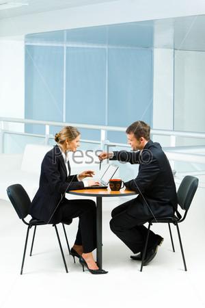 Бизнес леди сидит напротив бизнесмена за столом и печатает что-то на ноутбуке