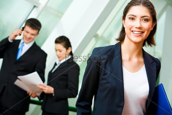 Фотография на тему Сотрудница офиса в деловом костюме держит в руках папку и стоит на фоне коллег