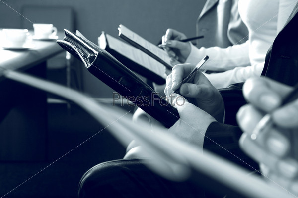 Черно-белое фото людей сидящих в ряд с записными книжками