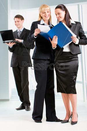 Деловые женщины обсуждают новые документы в офисе