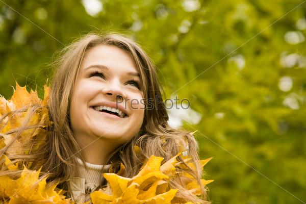 Фотография на тему Красивая девушка с осенними листьями смотрит вверх и улыбается