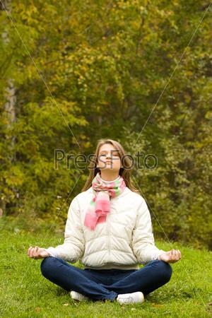 Девушка сидит на зеленой поляне и медитирует