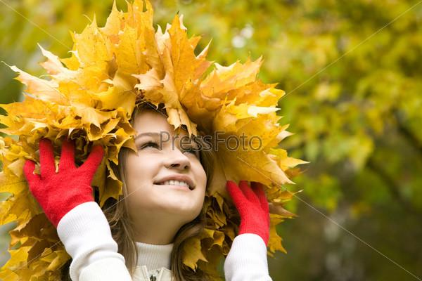 Счастливая девушка стоит в лесу держа на голове венок из осенних листьев