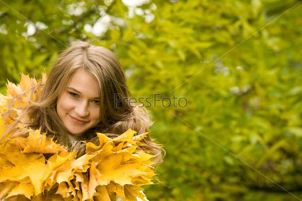 Девушка стоит с улыбкой в ожерелье из осенних листьев