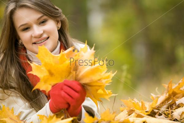 Красивая девушка с букетом осенних листьев