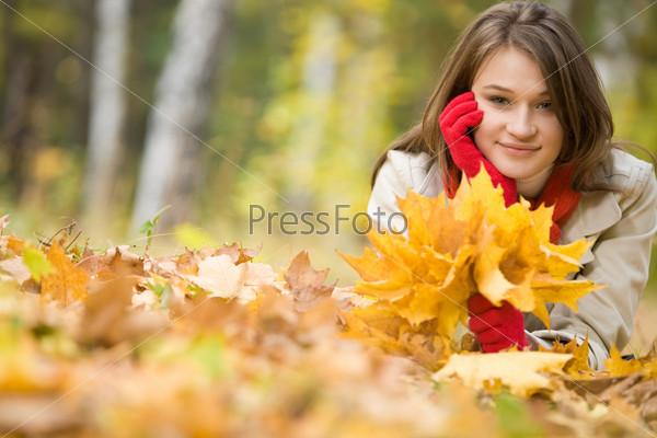 Девушка с букетом осенних листьев лежит на поляне в лесу