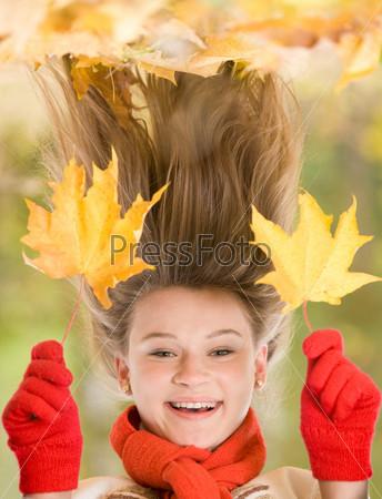 Смешная девушка в красных перчатках и шарфе в осеннем лесу