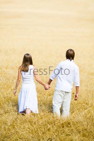 Влюбленная пара идет по пшеничному полю держась за руки