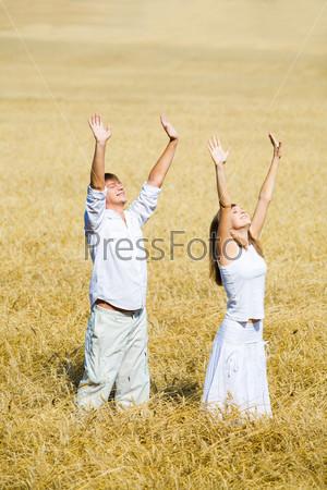 Счастливая пара стоит посреди пшеничного поля подняв руки вверх