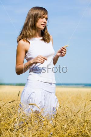 Задумчивая девушка стоит в поле держа в руках колосок