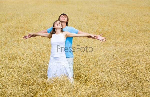 Молодая пара стоит раскинув руки на поле