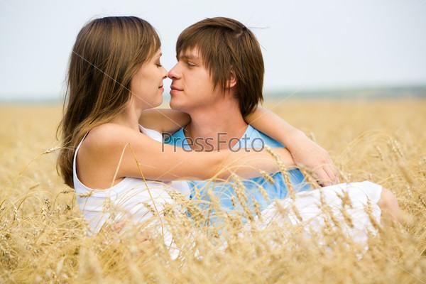 Молодой человек держит на руках свою подругу среди пшеничных колосьев