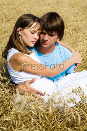 Задумчивая пара обнявшись сидит среди пшеничных колосьев