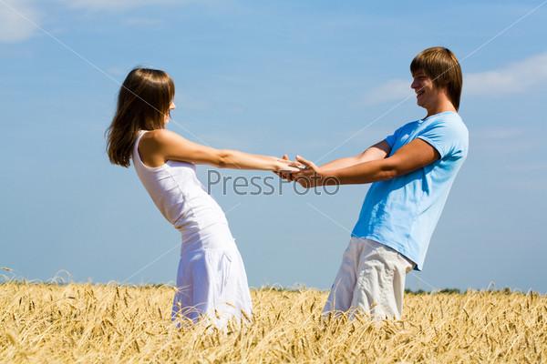 Фотография на тему Влюбленная пара держится за руки на фоне неба