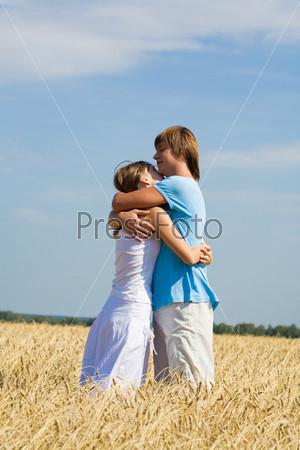 Фотография на тему Влюбленная пара стоит обнявшись в поле