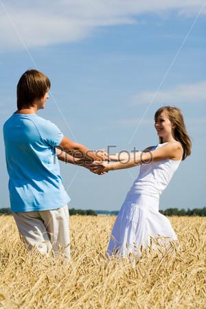Молодая пара кружится в поле держась за руки