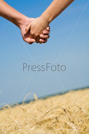 Крупный план скрепленных рук на фоне поля и неба