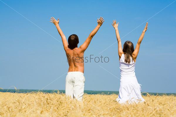 Парень с девушкой стоят в поле подняв руки к небу