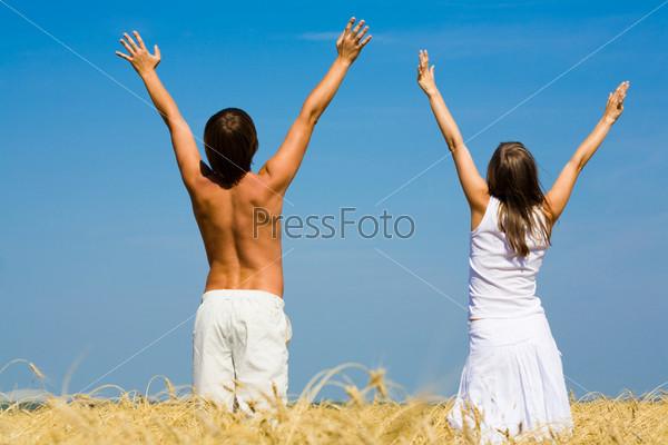 Молодая пара стоит спиной к камере подняв руки вверх