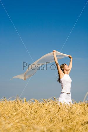 Счастливая девушка стоит в поле с шарфом в руках