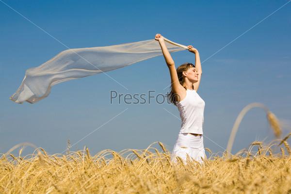 Красивая девушка с развевающимся белым шарфом в руках на фоне неба